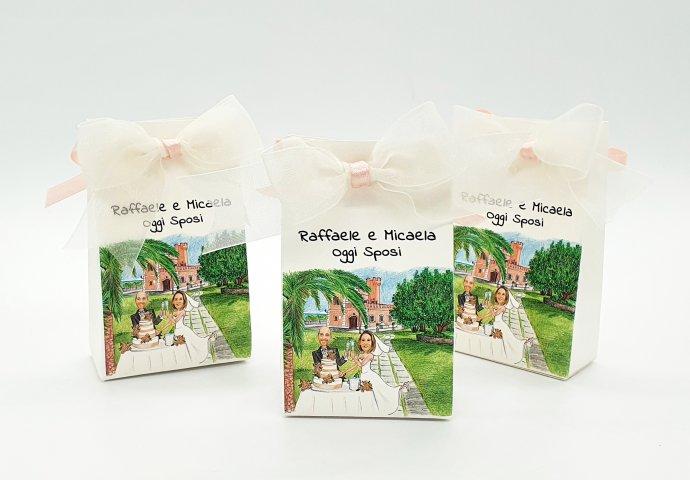 Scatolina porta confetti a sacchetto, personalizzata con scenetta caricatura fedele di sposi che tagliano la torta in location