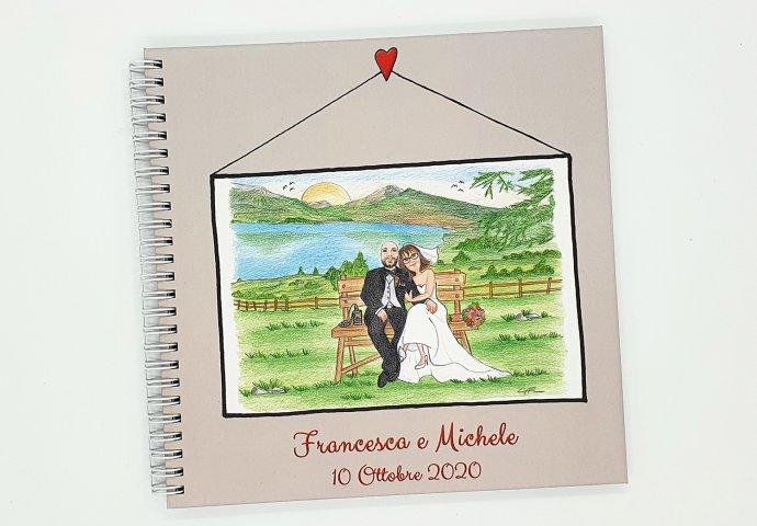 Guestbook con rilegatura a spirale e stampa disegno caricatura fedele di sposi seduti abbracciati su una panchina e nello sfondo un lago.