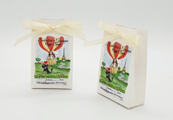 Scatolina porta confetti a sacchetto, personalizzata con scenetta caricatura fedele di sposa in mongolfiera che cerca di rirare su lo sposo